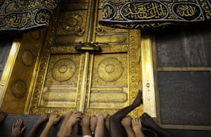 Pilgrims touch Islam's holiest shrine, the Kaaba, at the Grand Mosque
