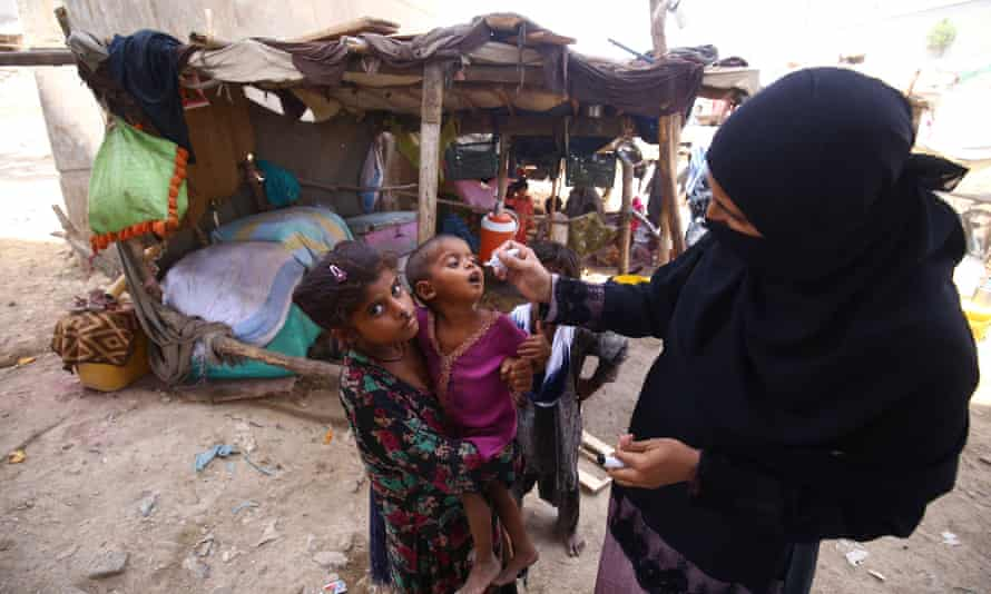 A health worker administers polio vaccine to children