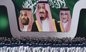 Newly graduated Saudi air force officers march in front of a banner bearing portraits of Crown Prince Mohammed bin Salman, his father King Salman, and Crown Prince Mohammed bin Nayef.