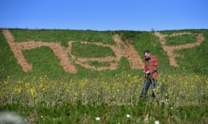 EU supporter Fred Powada stands next to a help sign he made in the grass with weedkiller in Laurenckirk, Scotland.