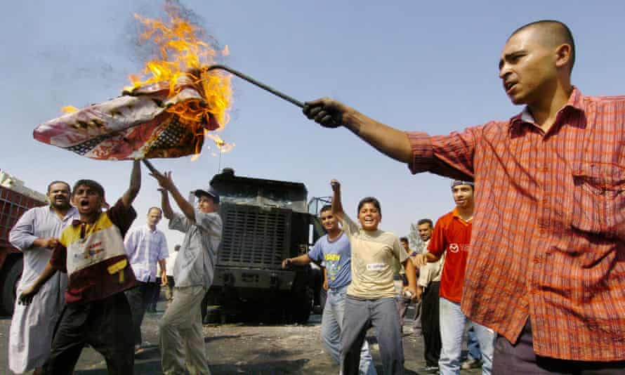Iraqi youths burn a US flag on the outskirts of Baghdad in 2004.