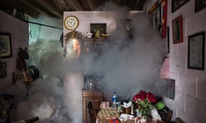 A room in a house in Santa Tecla fills with smoke as it is fumigated