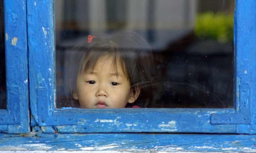 A North Korean child peers through a window in Hyangsan province.