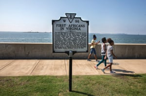 Young girls walk past a sign denoting the 400th anniversary of the landing of the first enslaved Africans in English-occupied North America at Point Comfort in 1619.