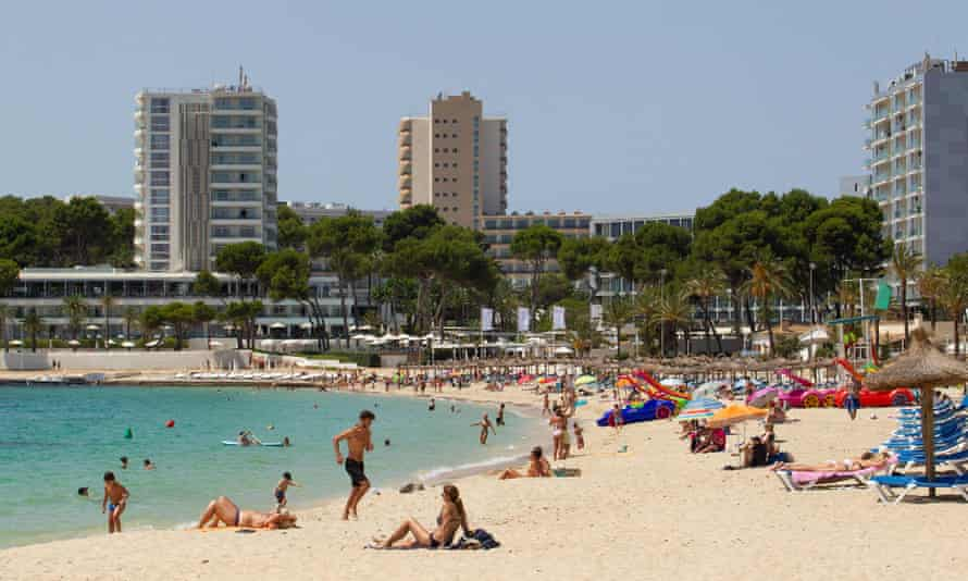 People enjoy a day out at Magaluf Beach in Calvia on the Spanish island of Mallorca. The cross-party group advises that Covid security should be improved at all points of entry into the UK.