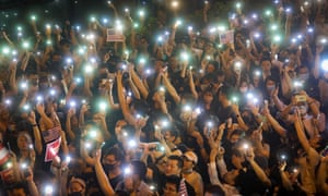 Protesters hold up mobile phones at a rally in Hong Kong