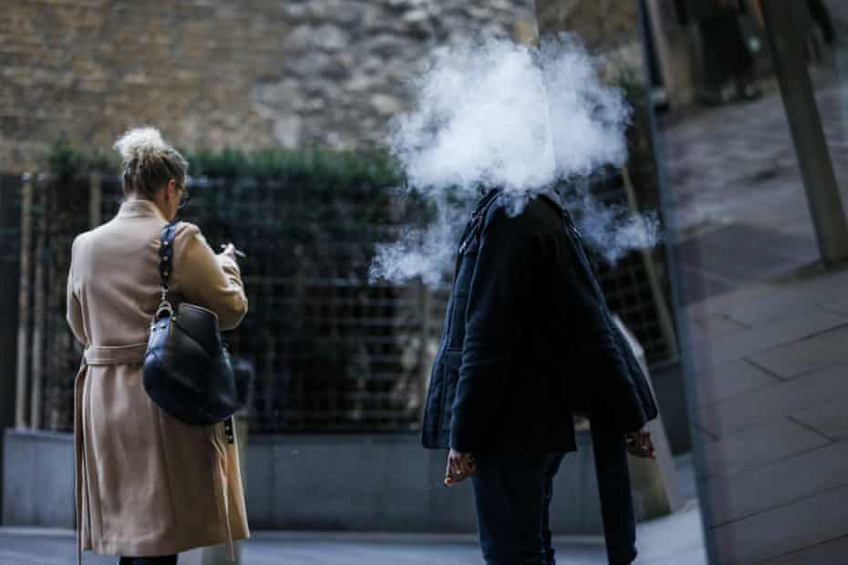 a smoker and a person vaping in london, uk