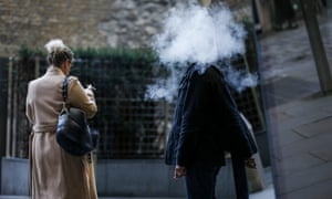 A pedestrian stands surrounded in a cloud of vapour after exhaling from a vape device as a pedestrian smoking a cigarette passes in London