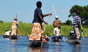 Boats men women pole river delta Botswana