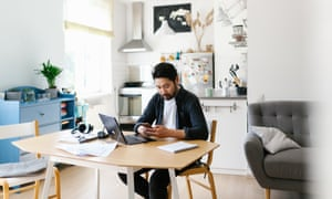 Asian man using smart phone while working from home<br>Photo series of japanese man working from home as a freelancer, making conference calls and discussing projects.
