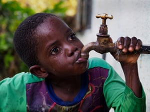Lead poisoning victim Gift Phiri, 6, drinks in his backyard in Chowa, the heavily polluted township next to the closed lead mine.