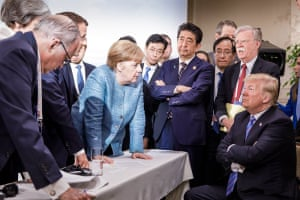 Donald Trump (right) talks with German chancellor Angela Merkel, surrounded by other G7 leaders and their advisers.
