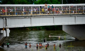 Honduran migrants heading in a caravan to the US wait to help people get down to the Suchiate River.