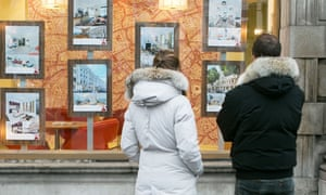 People looking at listings in an estate agent's window.