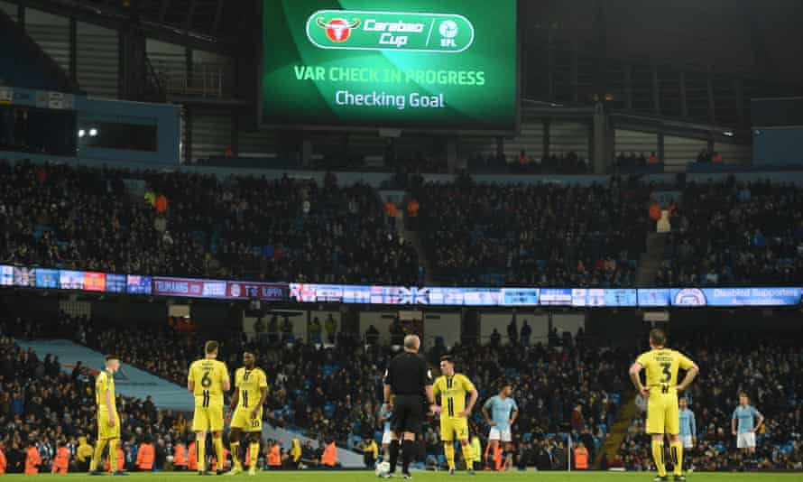 The players and referee wait for the VAR decision before Manchester City are awarded a goal against Burton in January 2019