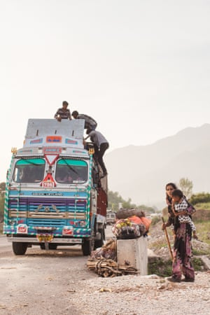 A nomadic family lift their belongings on to a truck