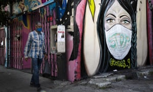A man wearing a face mask walks past a mural in South Central Los Angeles. In November 2020, California is reaching an unwelcome coronavirus record: its 1 millionth positive test.