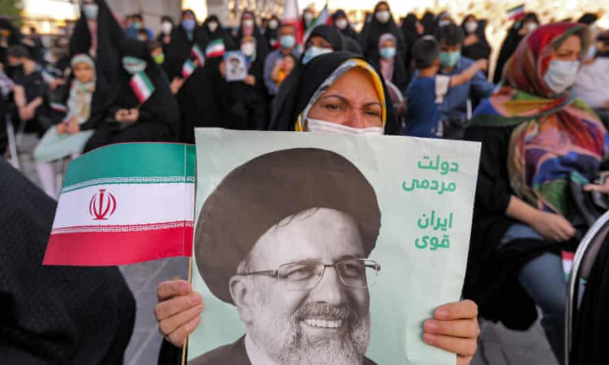 A woman holds a poster of Ebrahim Raisi, with text in Persian reading 'government of the people, strong Iran', as supporters celebrate his victory in Tehran.