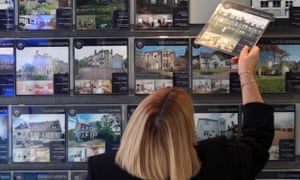 A woman looks at houses for sale