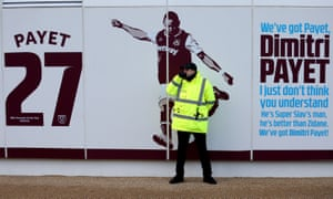A steward stands in front of Dimitri Payet signage