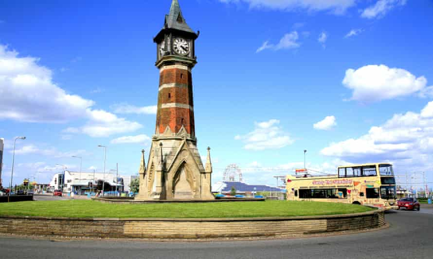 The clock tower an open top bus and the funfair in the background at Skegness in Lincolnshire.