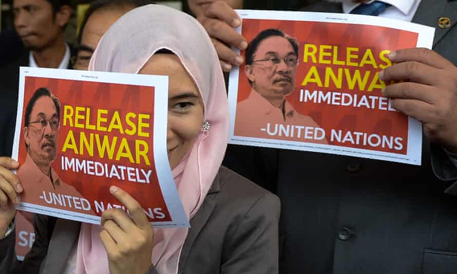 Opponents of Malaysia's government hold placards reading 'Release Anwar immediately'.