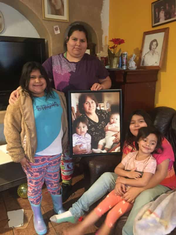 Maria Orozco in her home with her young daughters and niece, holding a photo of her mother, who died advocating for clean water.
