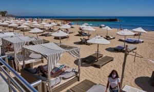 Beachgoers keep social distance on Praia do Tamariz in Estoril, near Lisbon.