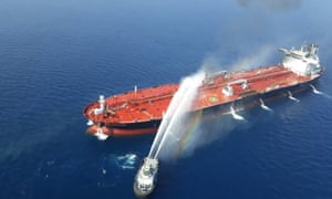 a boat douses a tanker on fire in the gulf of oman