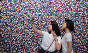 Two students take a selfie in front of a canvas filled with colourful buttons at the Hello, My Name is Paul Smith exhibition at the Today Art Museum in Beijing.