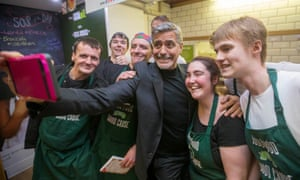George Clooney takes a selfie with staff as he visits Social Bite, Edinburgh, in November 2015.
