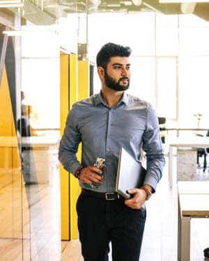 Successful Indian businessman with reusable cup and laptop in the office.