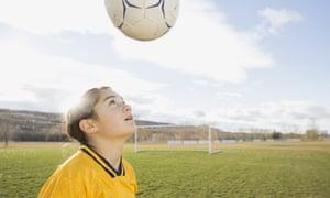 A girl heading a football