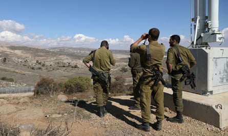 Israeli forces are seen near a border fence between the Israeli-occupied side of the Golan Heights and Syria.
