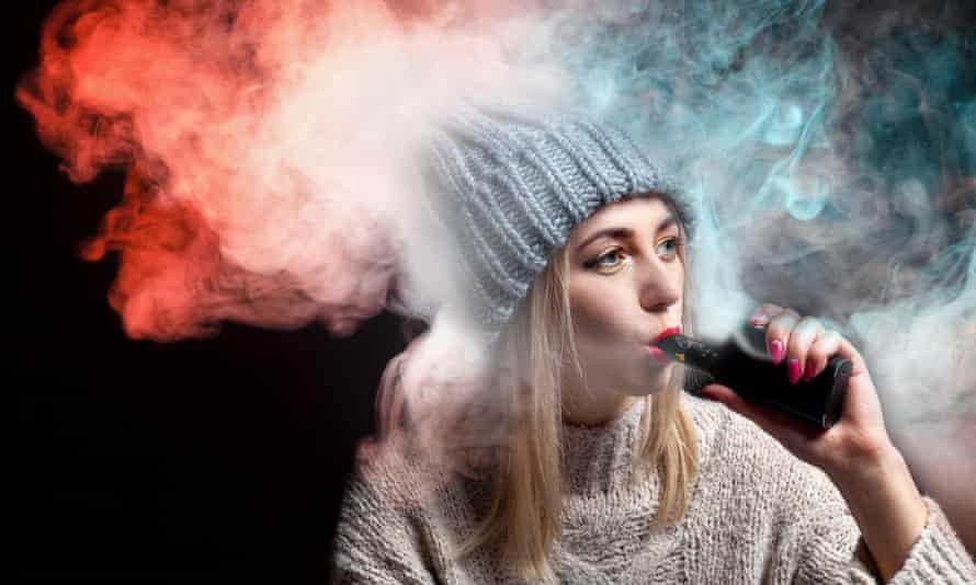 A young woman smoking an e-cigarette.