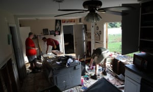 Men removing ruined items from a home following flooding in the wake of Hurricane Harvey in Dickinson, Texas.