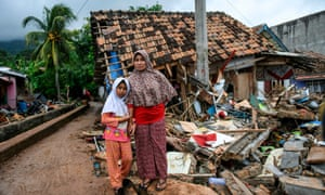 A girl holds her mother's hand in front of a collapsed house in Rajabasa in Lampung province on 25 December.