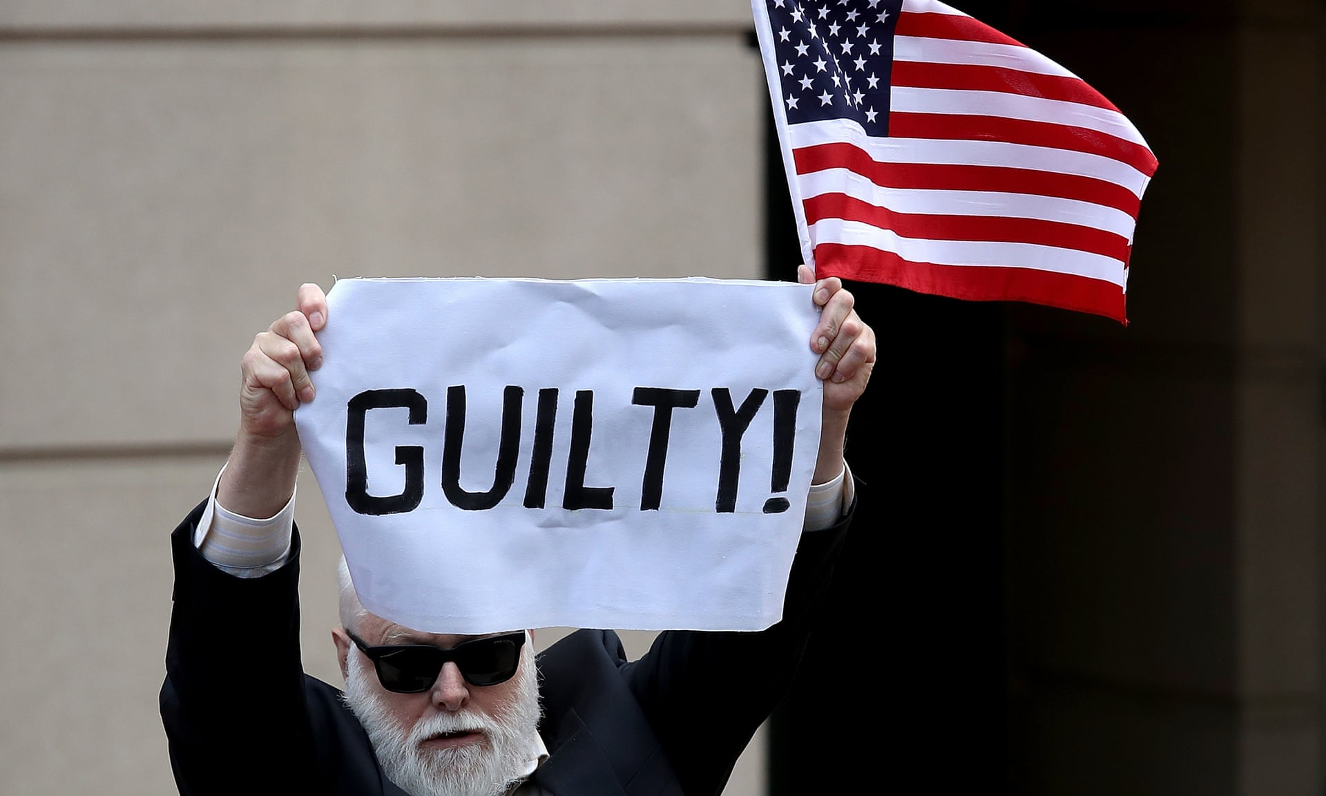 A lone protester holds up a sign and American flag outside the courthouse in Alexandria, Virginia, after Paul Manafort was found guilty on eight counts of fraud. — Photograph: Win McNamee/Getty Images.