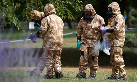 People in protective suits collect an item and photograph its location in Salisbury.