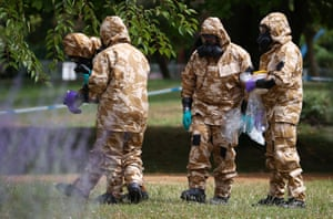 People in military hazardous material protective suits collect an item and photograph its location in Queen Elizabeth Gardens in Salisbury, 19 July