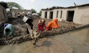 Villagers clear flood water from their houses in Jhado near Hyderabad, Pakistan