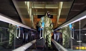 A passenger wearing protective garments arrives at the Josep Tarradellas Barcelona-El Prat Airport from London.