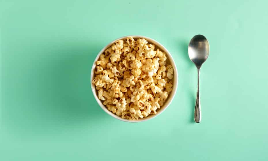 Pop corn in a bowl with spoon next to it, on green background