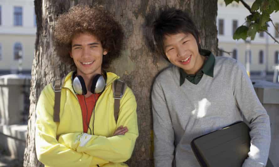 Teenage boys standing by tree