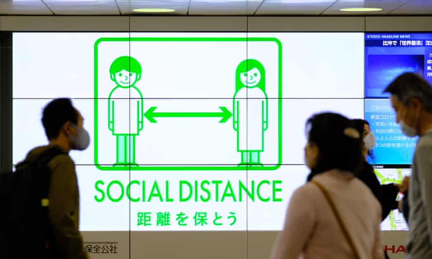 A Covid health sign at a train station in Tokyo's Shinjuku district