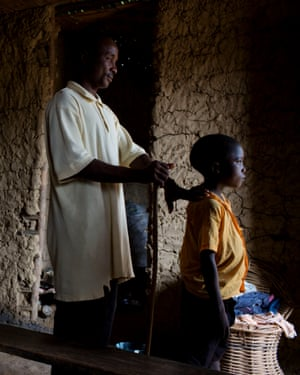 Varney N Steward, who set up a school despite being blind and destitute, is led along by his son at his school in Lowah, Montserrado County.