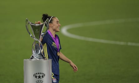 Lucy Bronze touches the Champions League trophy after collecting her winners' medal following Lyon's win against Wolfsburg last month.