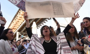 A woman holding a portion of the Torah during the morning prayer service at the Western Wall, in Jerusalem.