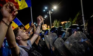 Protesters demonstrate in front of the Romanian government headquarters in Bucharest on 10 August.