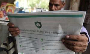 an Indian man reading a newspaper with a full back page advertisement from WhatsApp